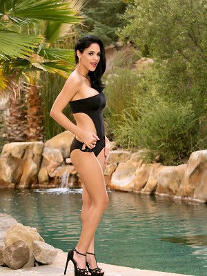 Jasmine Caro lays out by the pool and takes off her black swimsuit.